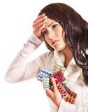 Mujer con las píldoras y las tablillas de la toma del dolor de cabeza. Foto de archivo