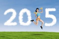 Mujer con las pesas de gimnasia que forman el número 2015 Imagen de archivo