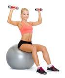Mujer con las pesas de gimnasia que se sientan en bola de la aptitud Fotografía de archivo