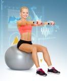 Mujer con las pesas de gimnasia que se sientan en bola de la aptitud Fotografía de archivo libre de regalías