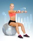 Mujer con las pesas de gimnasia que se sientan en bola de la aptitud Imágenes de archivo libres de regalías