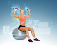 Mujer con las pesas de gimnasia que se sientan en bola de la aptitud Imagenes de archivo