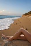 Mujer con las piernas arenosas que se relajan en una playa tropical Fotos de archivo libres de regalías