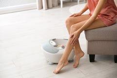 Mujer con las piernas hermosas que se sientan cerca de baño del pie en casa, primer con el espacio para el texto imagenes de archivo