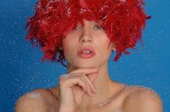 Mujer con las plumas rojas en la nieve Fotos de archivo libres de regalías