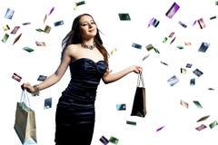 Mujer con las tarjetas de crédito que llueven sobre ella Foto de archivo libre de regalías