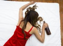 Mujer con las tetas al aire joven borracha que duerme en cama Foto de archivo libre de regalías