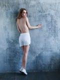 Mujer con las tetas al aire joven en los pantalones cortos y las zapatillas de deporte blancos Fotografía de archivo libre de regalías