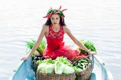 Mujer con las verduras en un barco en el agua Imagen de archivo libre de regalías