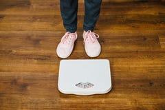Mujer con las zapatillas de deporte rosadas en escala del peso del cuarto de baño Imagen de archivo libre de regalías