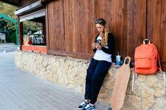 Mujer con longboard y mochila usando su teléfono celular mujer que envía un mensaje de texto de su teléfono móvil al aire libre Fotografía de archivo