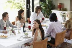 Mujer con los amigos que tienen un partido de cena en casa Imagen de archivo libre de regalías