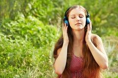 Mujer con los auriculares al aire libre Imagen de archivo libre de regalías