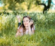 Mujer con los auriculares al aire libre Fotos de archivo libres de regalías