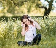 Mujer con los auriculares al aire libre Imagen de archivo