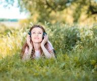 Mujer con los auriculares al aire libre Foto de archivo libre de regalías
