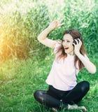 Mujer con los auriculares al aire libre fotos de archivo