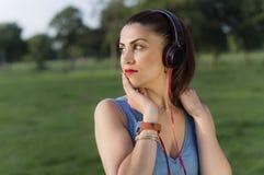 Mujer con los auriculares en el parque Fotos de archivo libres de regalías