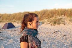 Mujer con los auriculares en la playa Imagen de archivo libre de regalías