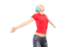 Mujer con los auriculares que escucha la música y el goce Imagen de archivo libre de regalías