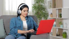 Mujer con los auriculares que hojea el contenido del ordenador portátil en casa almacen de video