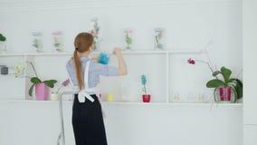 Mujer con los auriculares que limpian el polvo de estante en el hotel almacen de video
