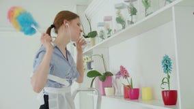 Mujer con los auriculares que limpian el polvo de estante en el hotel almacen de metraje de vídeo