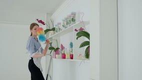 Mujer con los auriculares que limpian el polvo de estante en el hotel metrajes