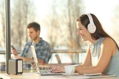 Mujer con los auriculares que mecanografía en un ordenador portátil Fotos de archivo libres de regalías