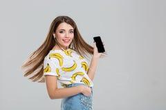 Mujer con los auriculares que muestran la pantalla en blanco del smartphone Imagen de archivo