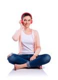 Mujer con los auriculares que se sientan en el piso, tiro del estudio, aislado Foto de archivo