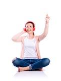 Mujer con los auriculares que se sientan en el piso, tiro del estudio, aislado Imagen de archivo