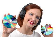 Mujer con los auriculares que sostienen los Cdes Fotografía de archivo