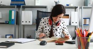 Mujer con los auriculares rojos en los hombros que cierran el libro y que se inclinan detrás almacen de metraje de vídeo