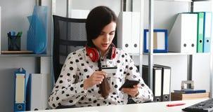 Mujer con los auriculares rojos en los hombros que incorporan el número de tarjeta de crédito en smartphone almacen de video