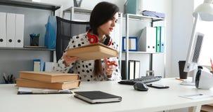 Mujer con los auriculares rojos en los hombros que manosean el libro con los dedos y que usan el ordenador portátil almacen de metraje de vídeo