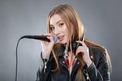 Mujer con los auriculares y el canto del micrófono Fotos de archivo