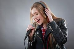 Mujer con los auriculares y el canto del micrófono Imágenes de archivo libres de regalías