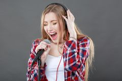 Mujer con los auriculares y el canto del micrófono Fotografía de archivo libre de regalías