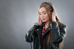 Mujer con los auriculares y el canto del micrófono Fotos de archivo libres de regalías