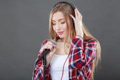 Mujer con los auriculares y el canto del micrófono Imagen de archivo