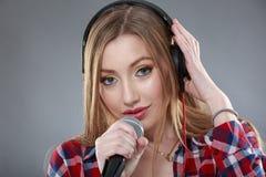 Mujer con los auriculares y el canto del micrófono Imagen de archivo libre de regalías