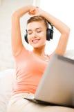Mujer con los auriculares y el ordenador portátil en casa Imágenes de archivo libres de regalías