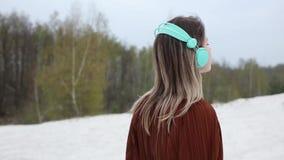 Mujer con los auriculares y la blusa del color de Borgo?a en fondo de los ?rboles de abedul almacen de metraje de vídeo