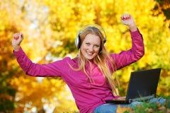 Mujer con los auriculares y otoño de la computadora portátil al aire libre Imagenes de archivo
