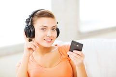 Mujer con los auriculares y smartphone en casa Foto de archivo libre de regalías