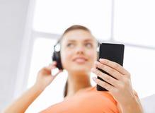 Mujer con los auriculares y smartphone en casa Foto de archivo