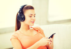 Mujer con los auriculares y smartphone en casa Imagen de archivo libre de regalías
