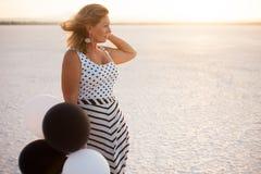 Mujer con los baloons en el lago de sal en Larnaca, Chipre imagenes de archivo