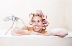 Mujer con los bigudíes en bañera fotos de archivo
